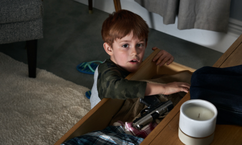 Young boy searching in open drawer for an unsecured gun among clothes