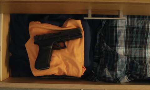 An unsecured gun in an open drawer with clothes