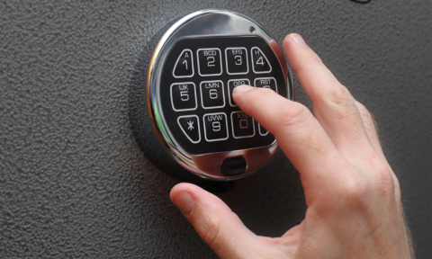 A hand entering the combination using the keypad on a gun safe